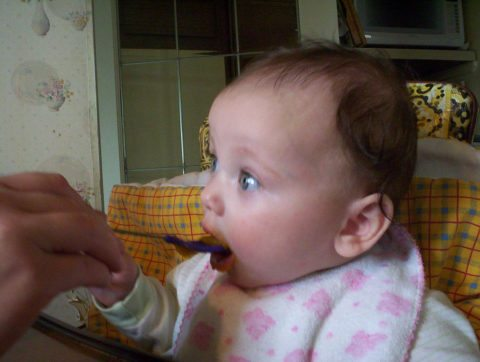 A sweet little baby eating mama's homemade baby food.