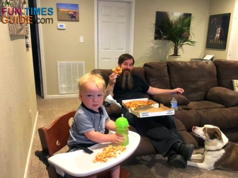 Dad and baby enjoying TV dinner night in the living room with a comfy couch and Keekaroo high chair.